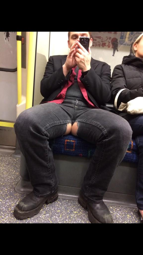 Manspread with holes in crotch of jeans