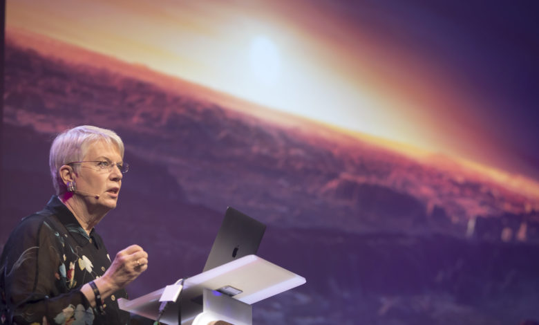 Jill Tarter giving a talk with a picture of an alien sunset in the background