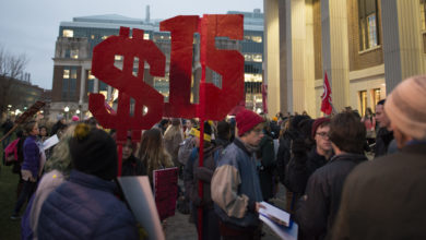 "crowd of protestors with a large sign that says ""$15"""